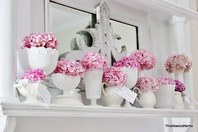 This collection of blooming hydrangeas brightens up this white mantel.