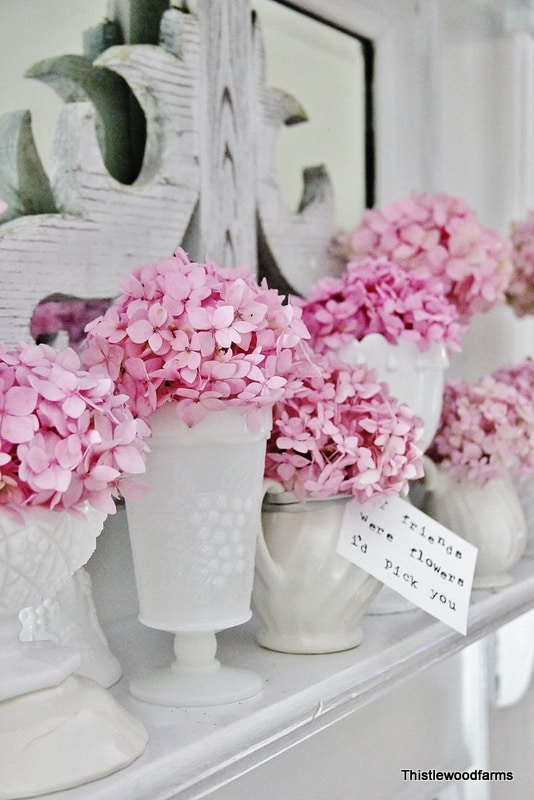 The different vases compliment the pink hydrangeas on the mantel.