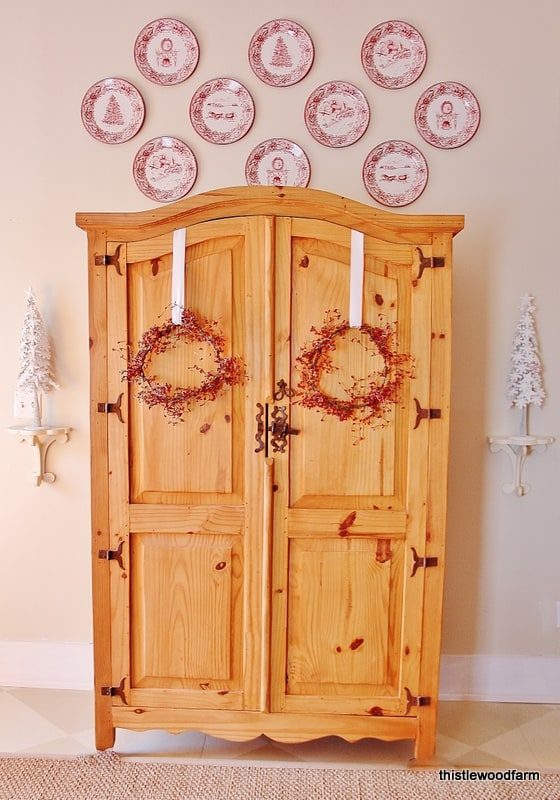 The armoire equipped with two red wreaths and coinciding white Christmas trees is holiday decor at its finest.