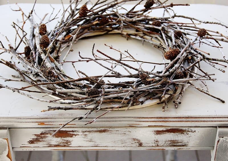 Glue pine cones to your branches then spray paint your entire finished wreath.