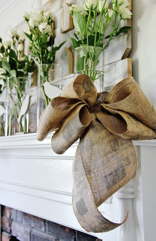 burlap bow on a mantel with flowers decorated for spring