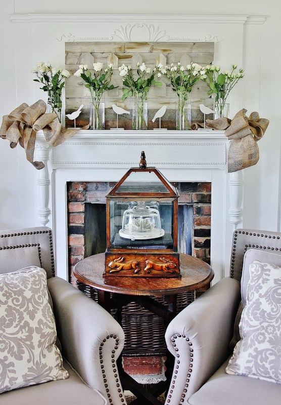 spring mantel with burlap bows and linen chairs and an antique table and flowers