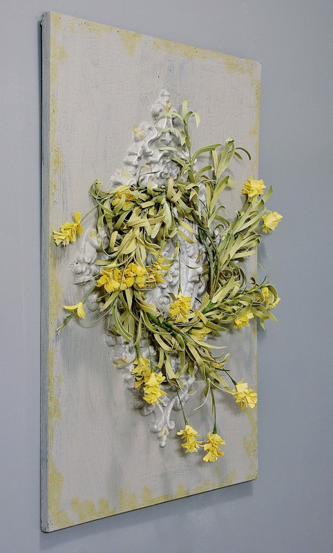 This distressed floral gray piece of artwork on the wall adds a unique farmhouse design touch.