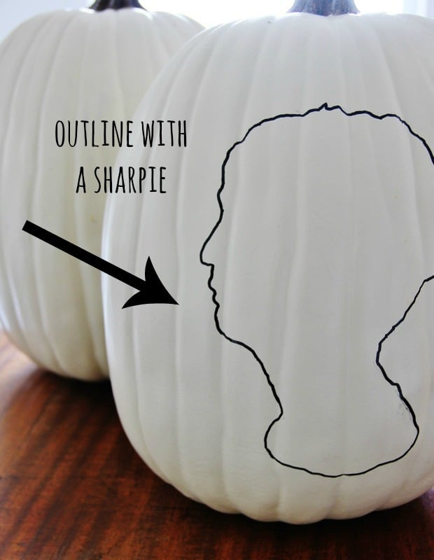 pumpkin silhouette traced onto white pumpkin with sharpie marker