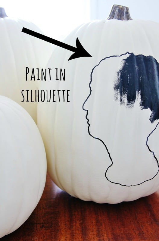 painted pumpkin silhouette on white pumpkin with black paint