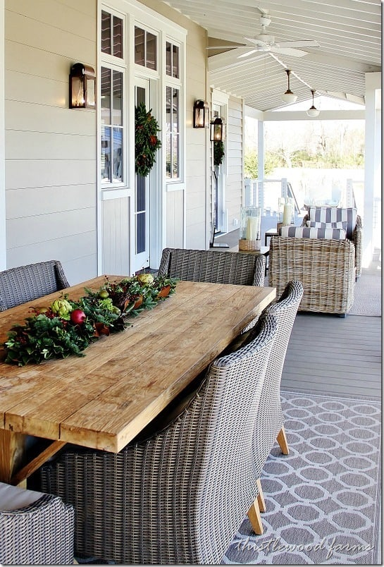 Farmhouse tables and wicker chairs are classic southern style decorating on this gorgeous and relaxing front porch