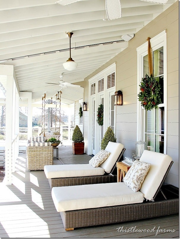 Magnolia wreaths and light linens on the back porch lounge chairs give this back porch a welcoming, relaxing feel