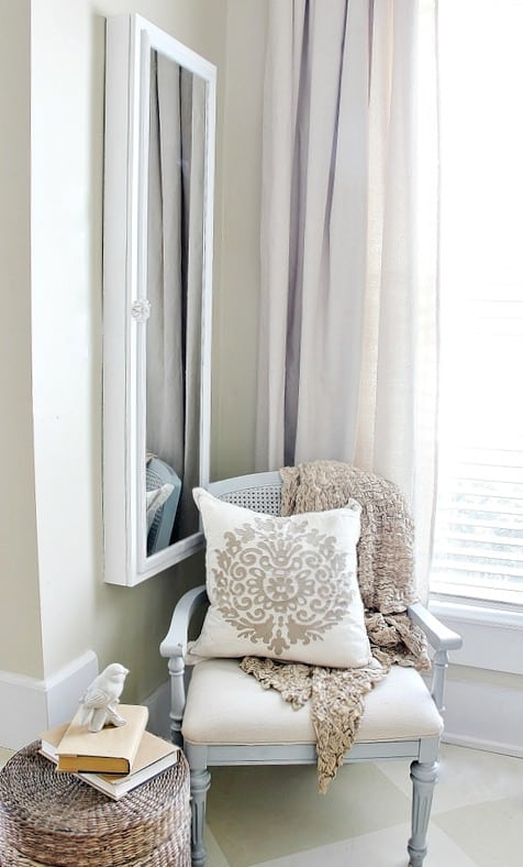hanging jewelry organizer in farmhouse bedroom with gray chair and khaki pillow