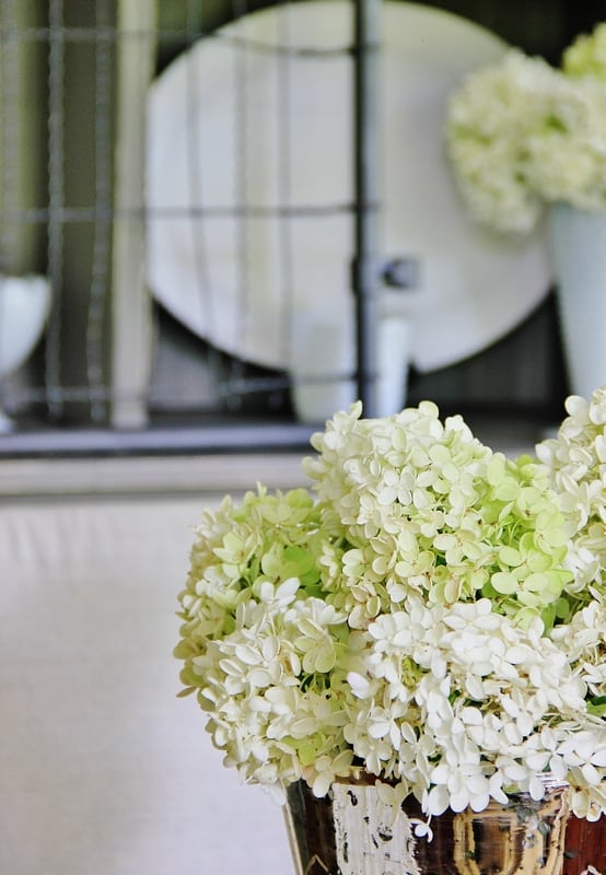 This vase of hydrangeas on the table beautifully echo the hydrangeas on the hutch in the back.