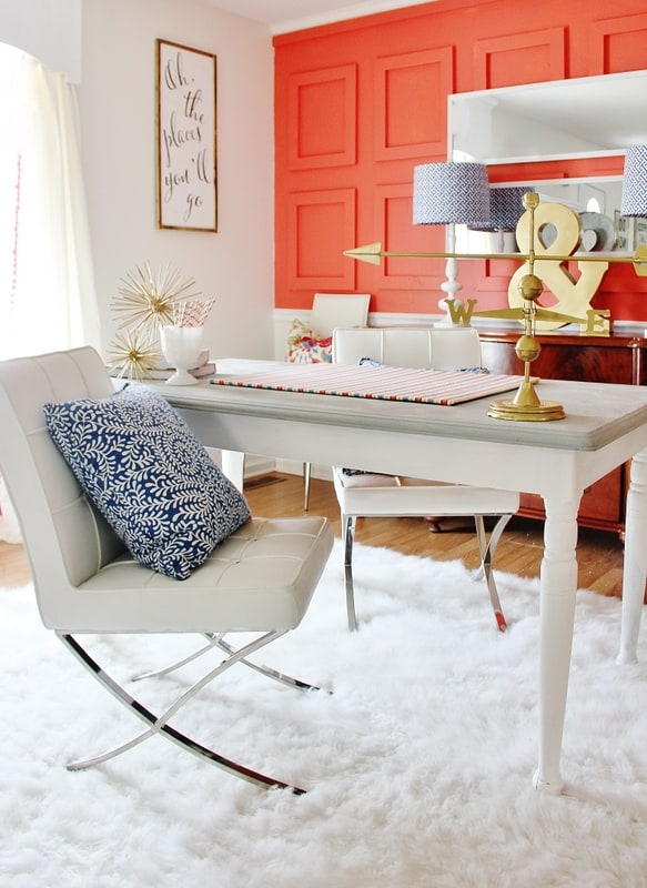 living room wall ideas with a wall painted coral white rug white chairs brass accessories