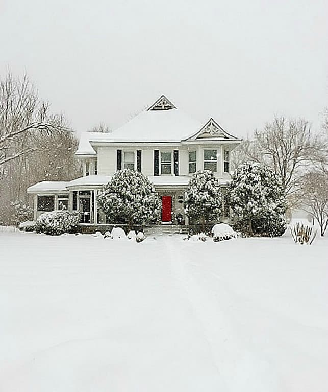winter farmhouse n snow with a red door