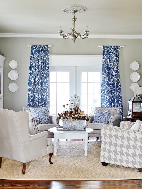 The blue window curtains in this living room pop against the gray walls.