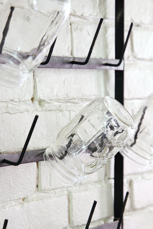 A vintage metal rack holds three mason jars on metal pegs hung on a white brick wall