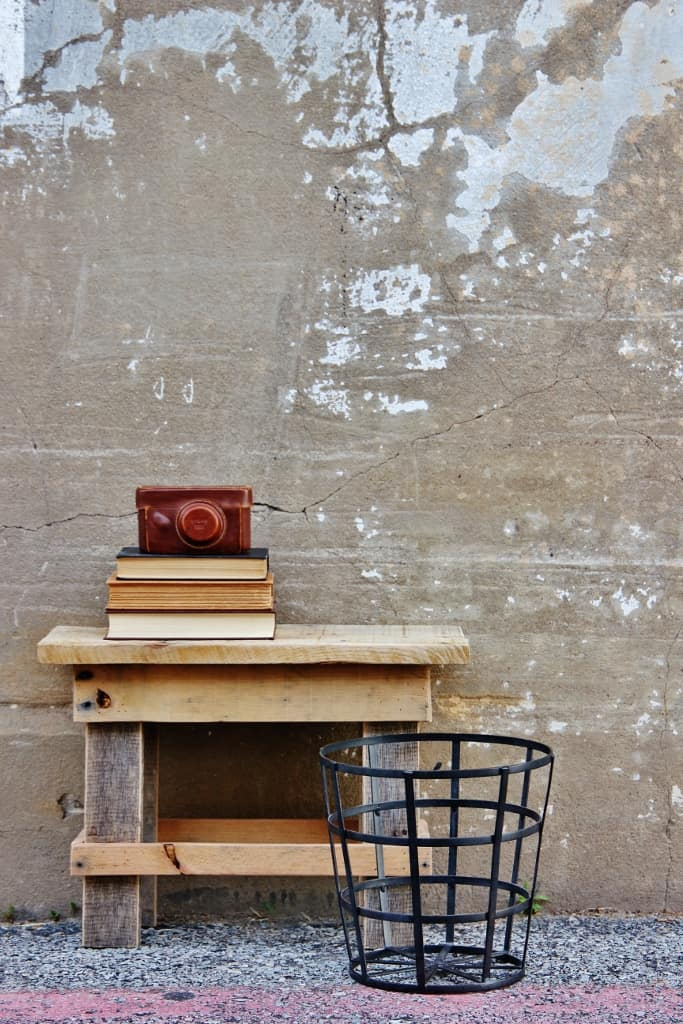 reclaimed wood stool on concrete with a leather camera and a stack of books