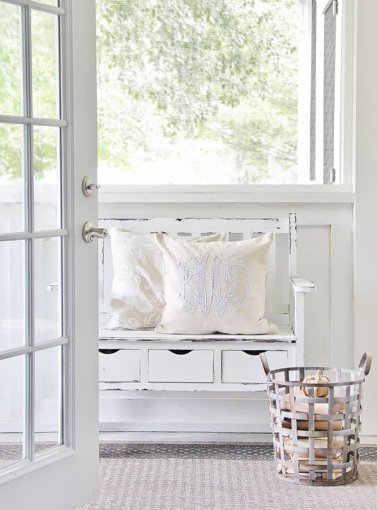These cute monogram pillows on the rustic mudroom bench add a personalized decor element to the space.