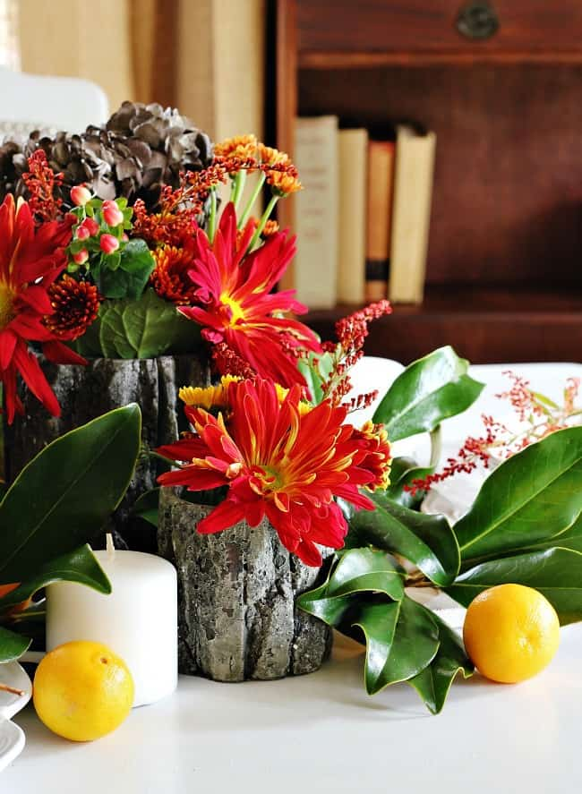 Log vases filled with brightly colored flowers make great center pieces.