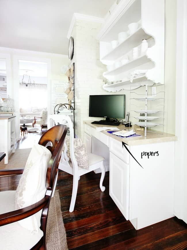 This desk area with papers everywhere needs organization.