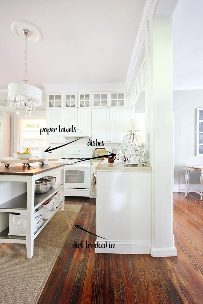 This white kitchen full of light has dirty dishes in the sink and dirt on the rug.