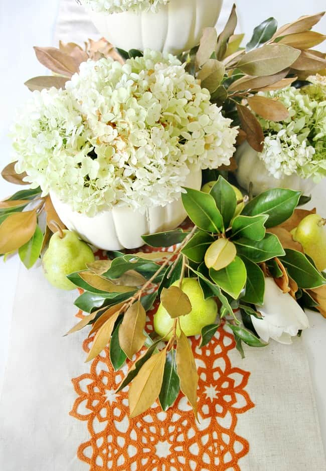 Create a beautiful centerpiece by hollowing out several faux pumpkins, then filling the center of each mason jar with hydrangeas.