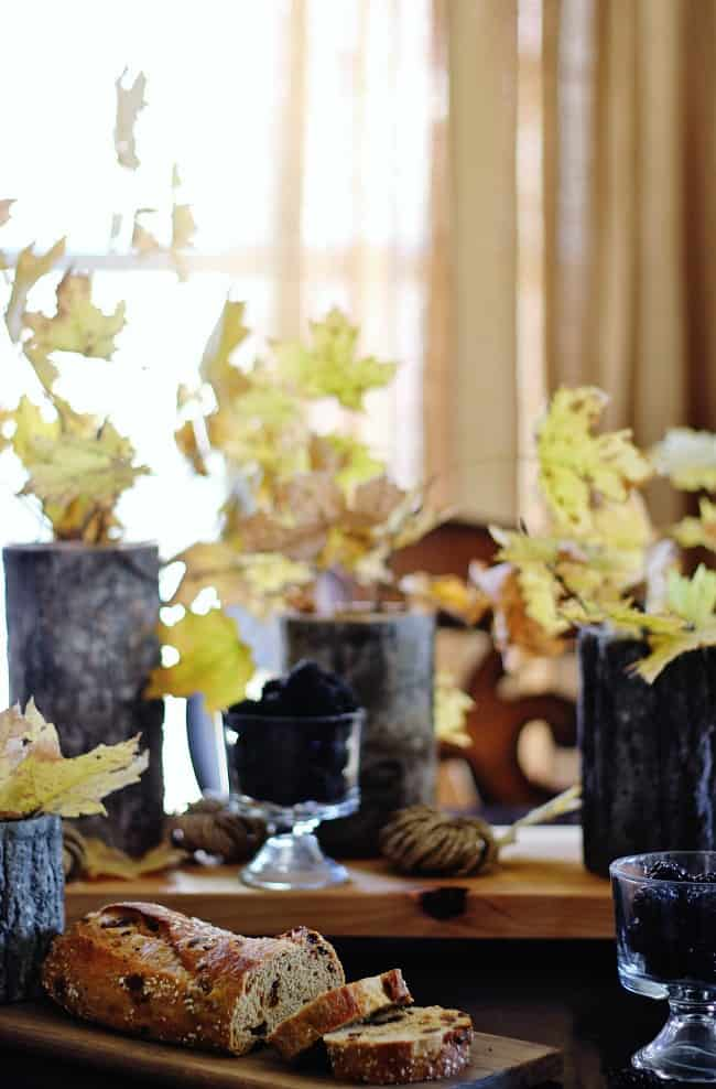 Wood vases filled with leaves are the perfect center pieces for this wooden coffee table.