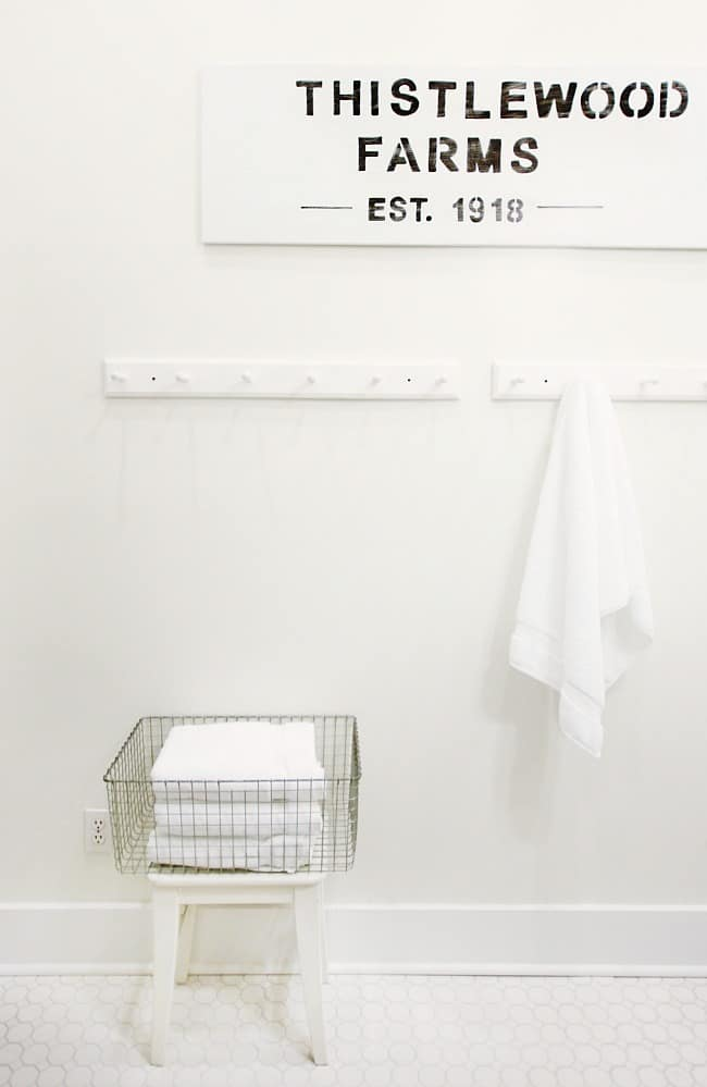 This thistlewood farms wood painted sign above the towel hooks adds fun decor to the wall.