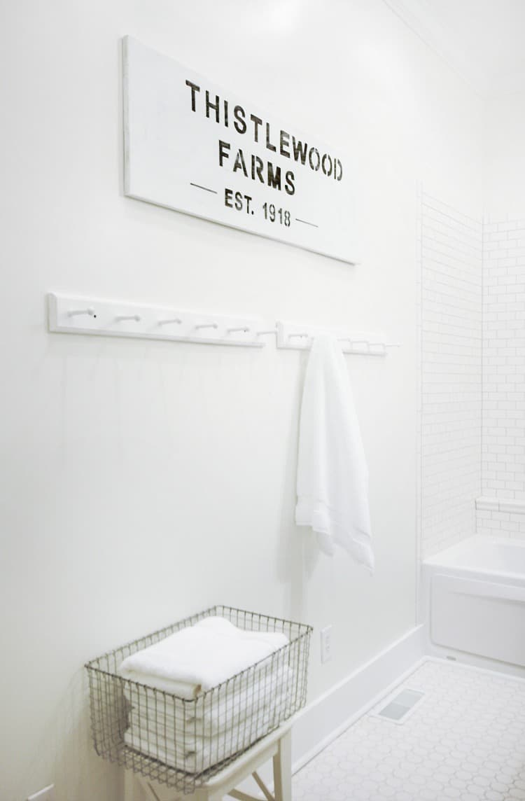 This thistlewood farms wood painted sign adds a cute element to this bathroom wall.