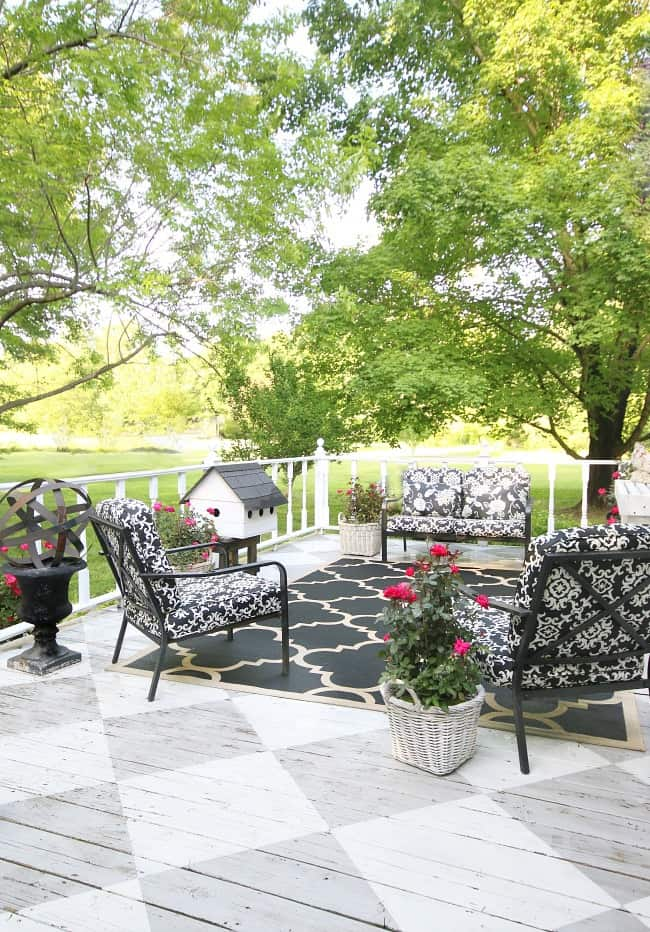 This black and white patio furniture pops against the wood porch.