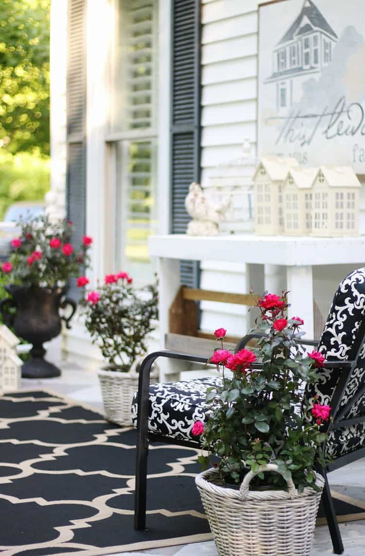 The bright pink flowers on this front porch compliment the black and white patio decor.