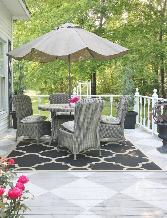 From the adorable window shutters to the charming patio table this back porch is quaint.