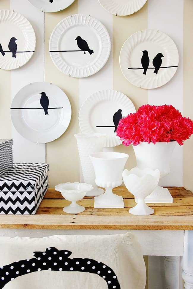 white plates on wall with bird decals and milk glass and pink flowers