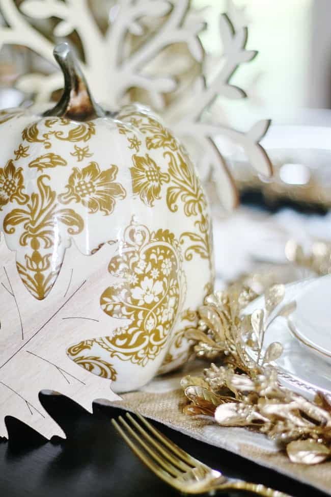 This gold and white painted pumpkin adds elegance to any dining room table.
