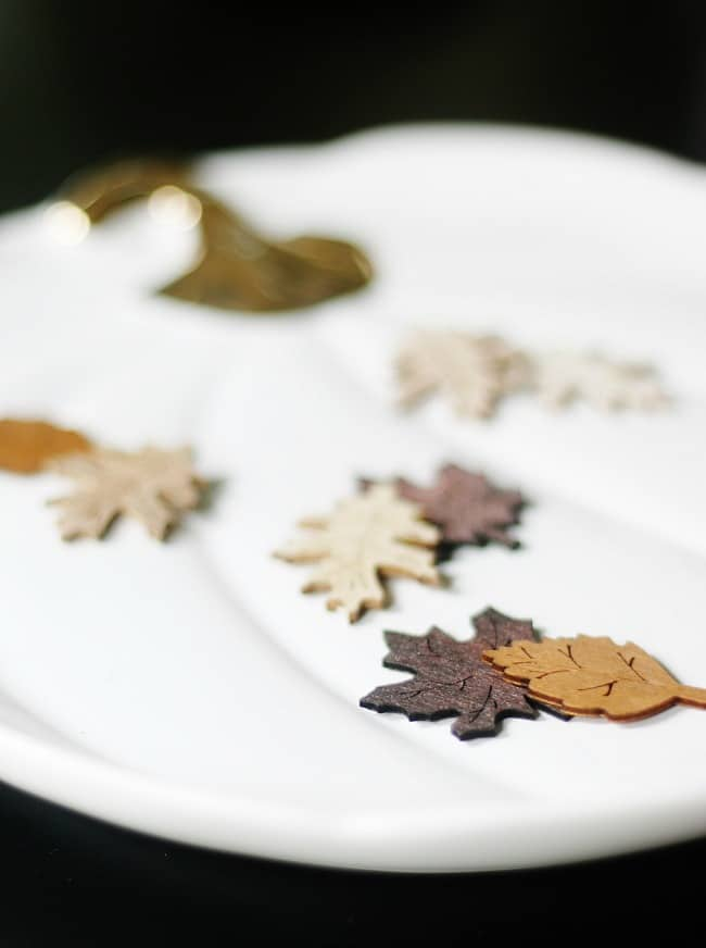 Use tiny wood decorations to decorate the platters and plates on your fall fining room table.