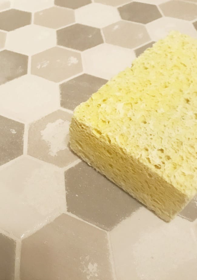 Carefully remove the top layer of grout with a sponge.