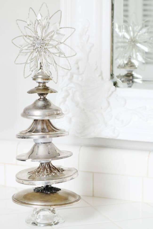 A DIY christmas tree made with silver bowl lids and topped with a glass decorative star
