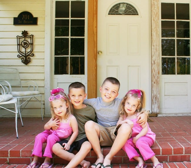 four kids sitting on before porch
