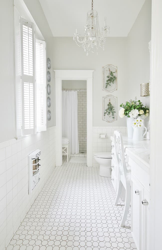 A white bathroom scene; white tile floor and wall, with light gray painted walls. White cabinets and white marble countertops on the vanity and white wooden chairs. Sitting on the counter are white vases with white, yellow, and green flowers