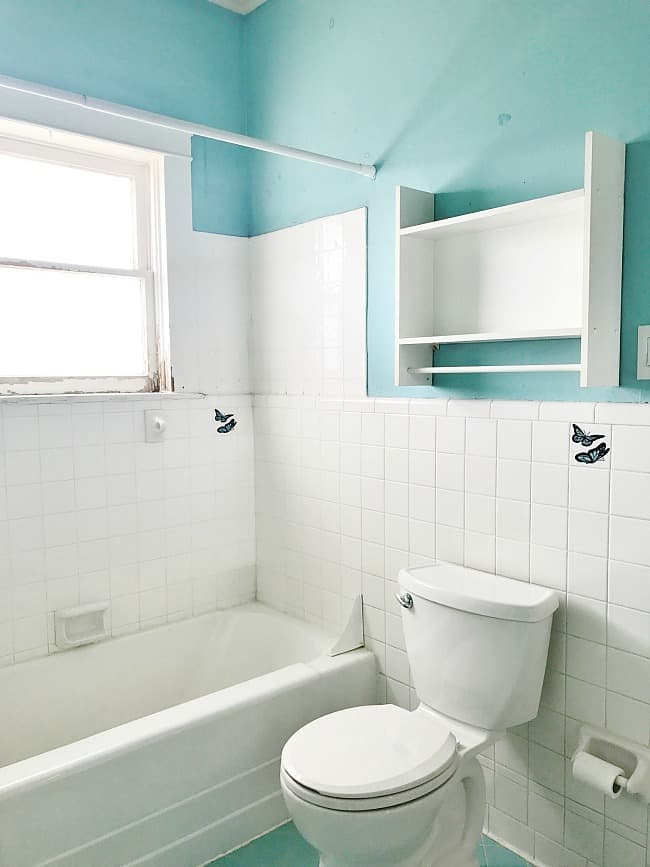 An old and outdated bathroom with grimey old white tiles and drab aqua blue paint