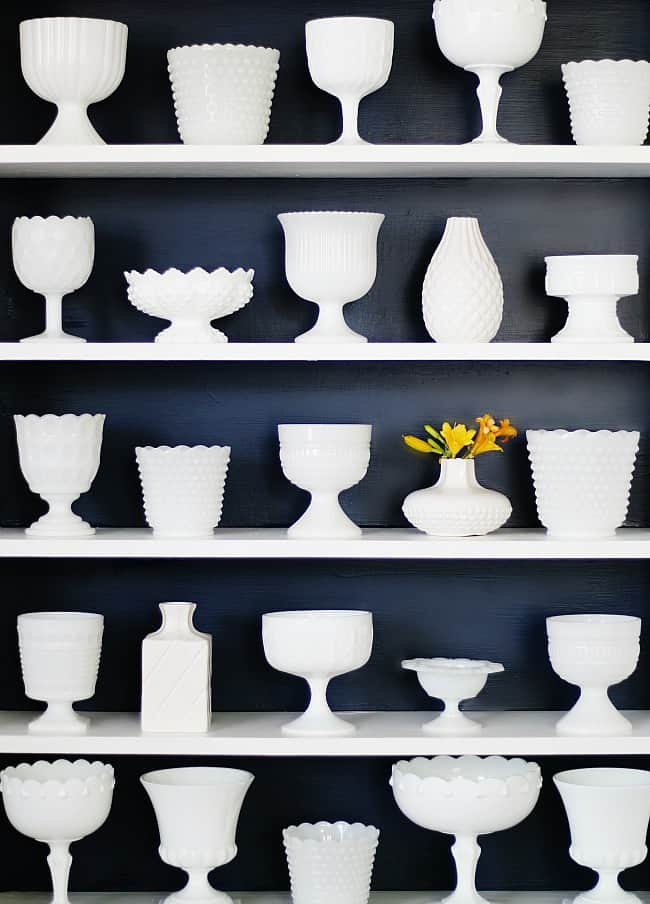 A built in bookshelf wall filled with white porcelain vases
