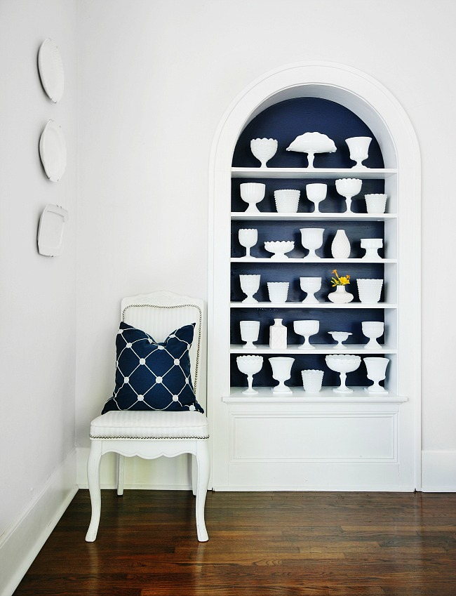 A built-in white bookshelf filled with white vases of different shapes and sizes collected from yard sales
