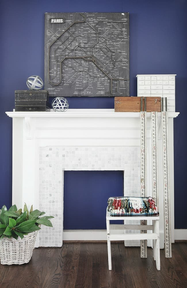 After the makeover: the white wood mantle is retiled with small ceramic and glass tiles. The wall is painted a stunning Indigo Blue from Sherwin-Williams