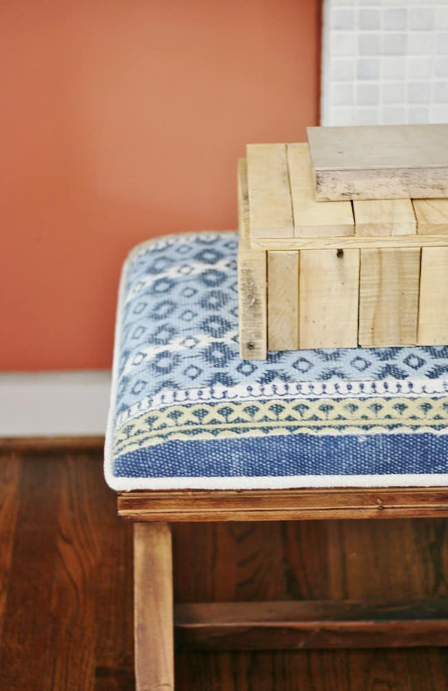 Wooden collectables box sitting on a bench with a blue and yellow patterned pillow