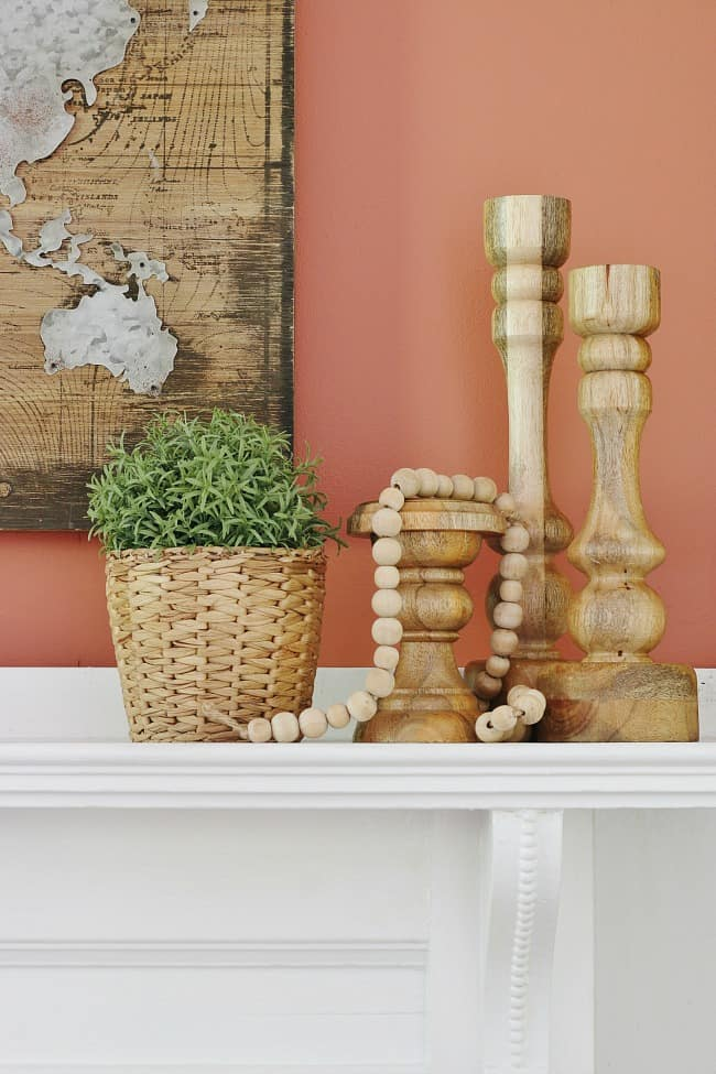 Wooden decorations, candle sticks, a thread of beads and a woven planer with greenery