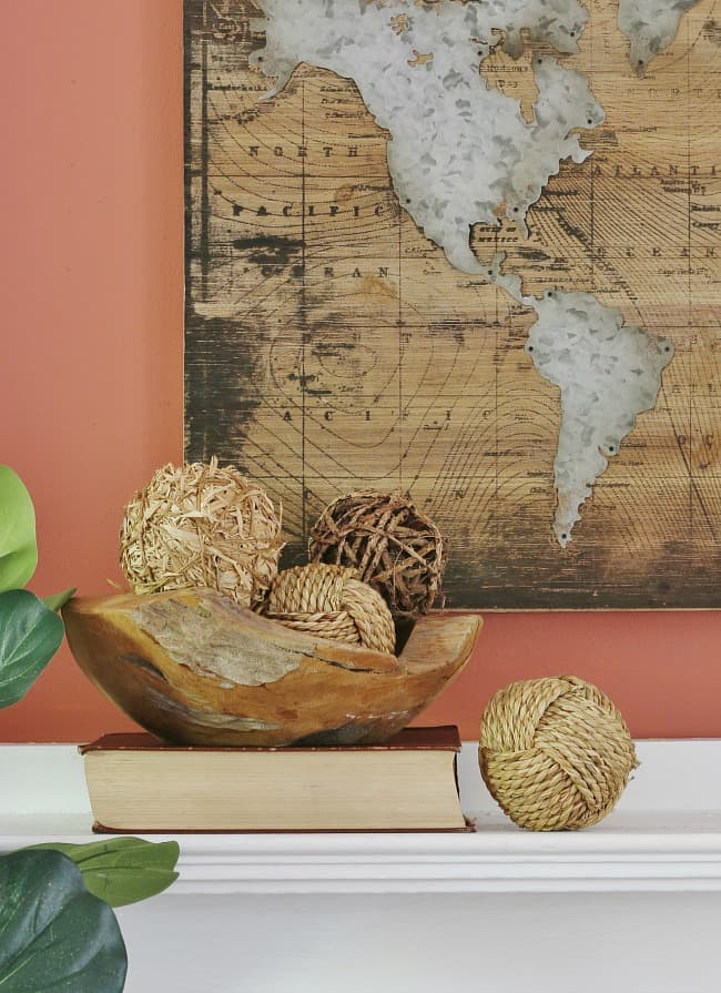 Artwork of a map of the world with a wooden bowl filled with balled twine sitting on top of a book