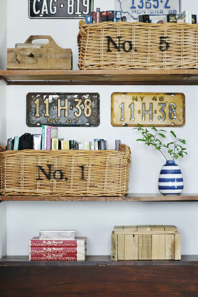 Yard sale finds make great home decor! These woven baskets are filled with books and decorated with metal letters. On the wall are vintage license plates and other yard sale finds.